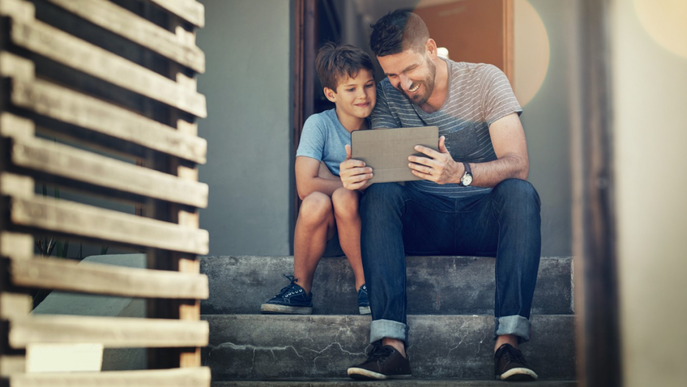 Father and son watching video on ipad