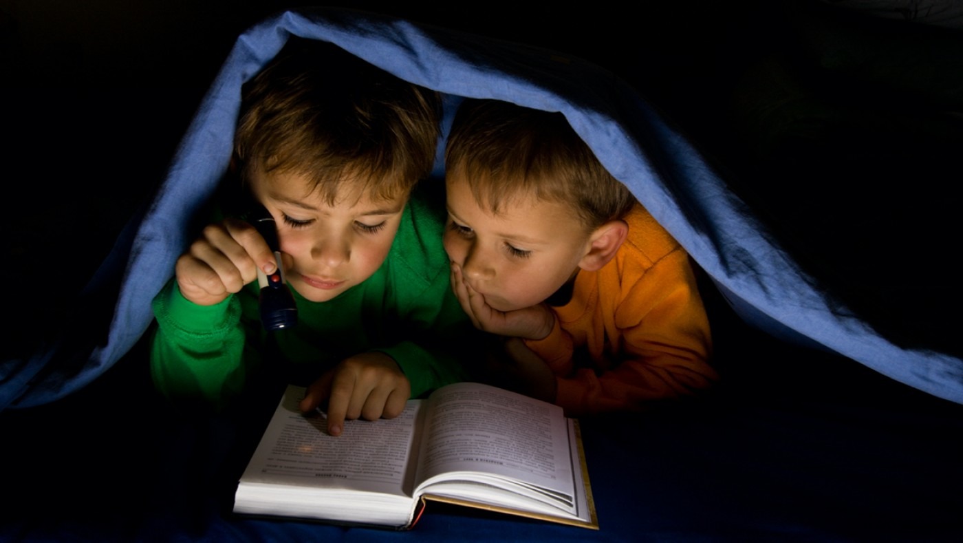 Kids reading under blanket during power outage