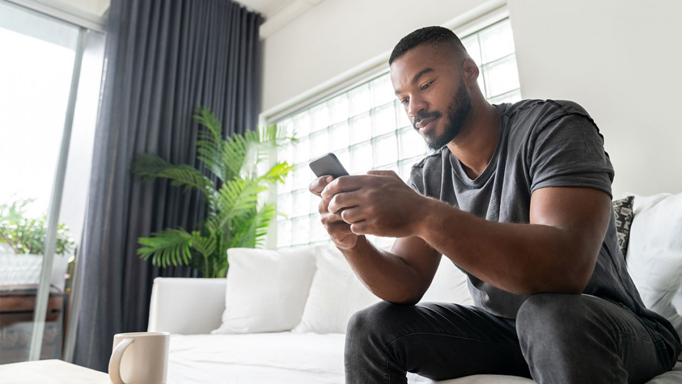 Man using cell phone on couch