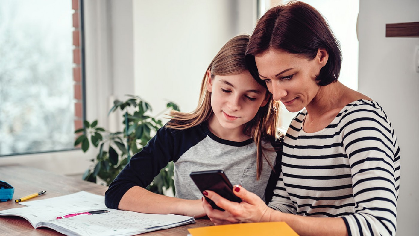 mom and daughter looking at a cell phone